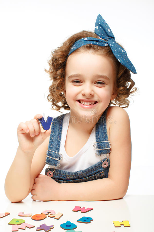 Free Little Girl Playing In The Alphabet. Shows The Letter V. Stock Photo - 37845650