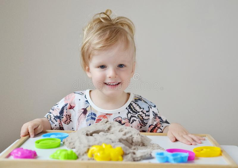 Little Girl Playing with Kinetic Sand at Home stock images
