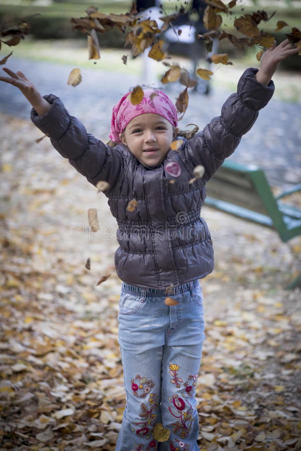 Little girl playing with leaves stock photo