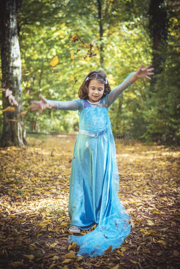 Little fashionable girl. Little girl playing with leaves in the wood,selective focus royalty free stock image