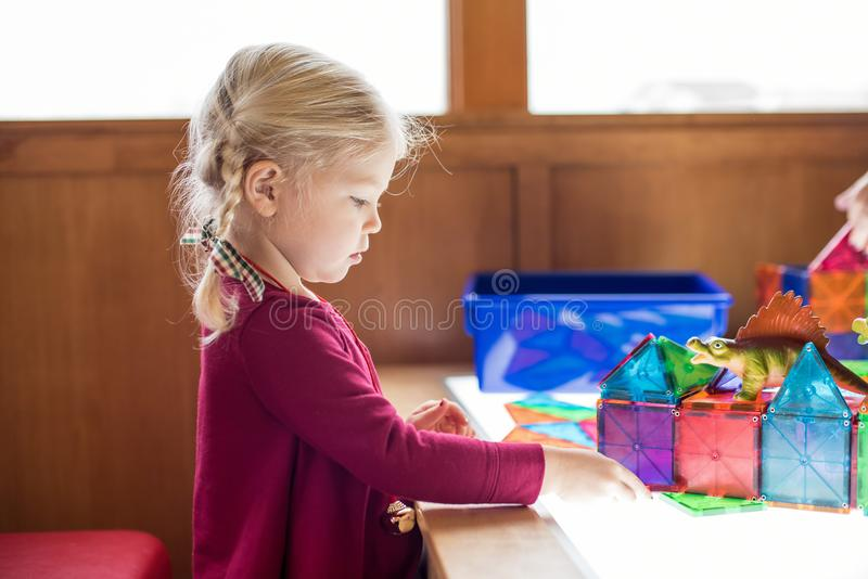 Little girl playing at light table with magnetic tiles. Preschool aged little girl playing at light table building with magnetic tiles royalty free stock photos