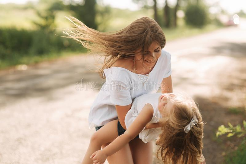 Little girl playing with mom in the park in summer day during the sunset spin around royalty free stock image