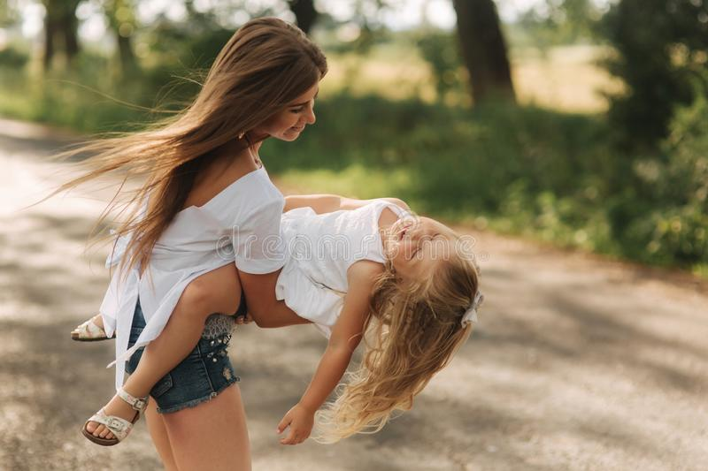 Little girl playing with mom in the park in summer day during the sunset spin around stock image