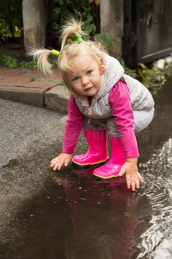A little girl is playing in the mud in a puddle, rainy weather royalty free stock photo