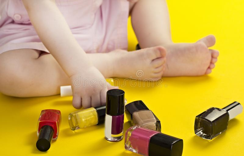 Little girl is playing with nail polish, yellow background, close-up, cosmetic stock images