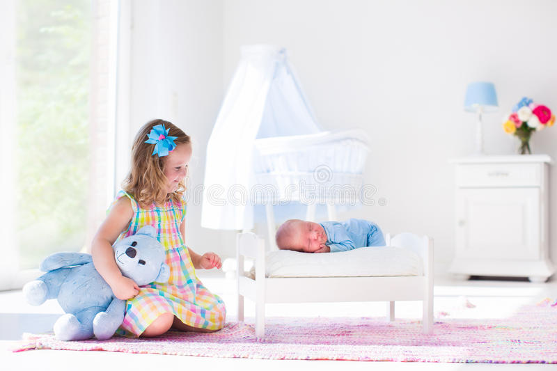 Little girl playing with newborn baby brother stock image
