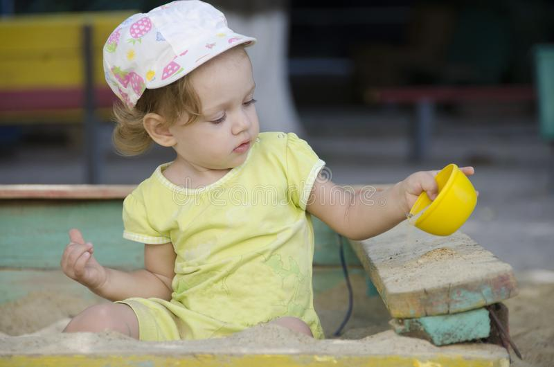 Little girl is playing in old sandbox royalty free stock photos