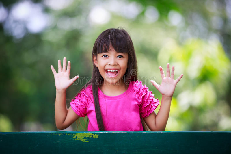 Little girl playing peek-a-boo. In the park stock image