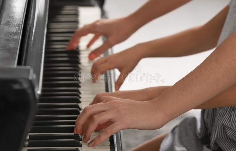 Little girl playing piano with teacher indoors stock images