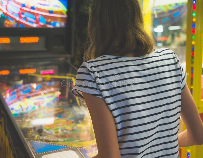 Little girl playing pinball game. royalty free stock photography