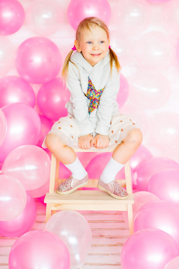Little girl playing with pink balloons. Little girl with blond hair playing with pink and beige balloons. Happy Birthday stock photos