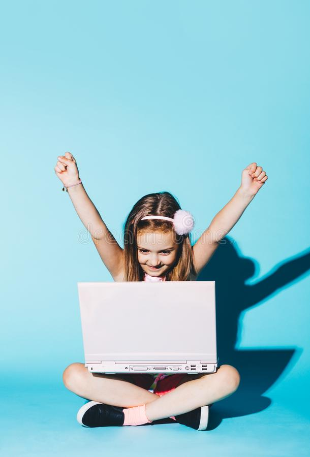 Little girl playing on a pink laptop, raising her hands up royalty free stock images