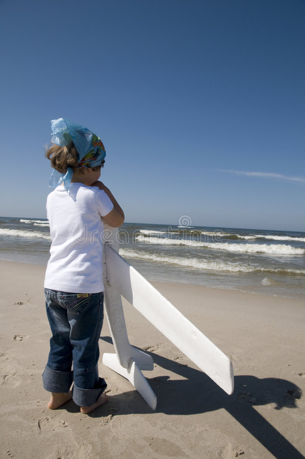Little girl playing with plane model. On the beach stock image