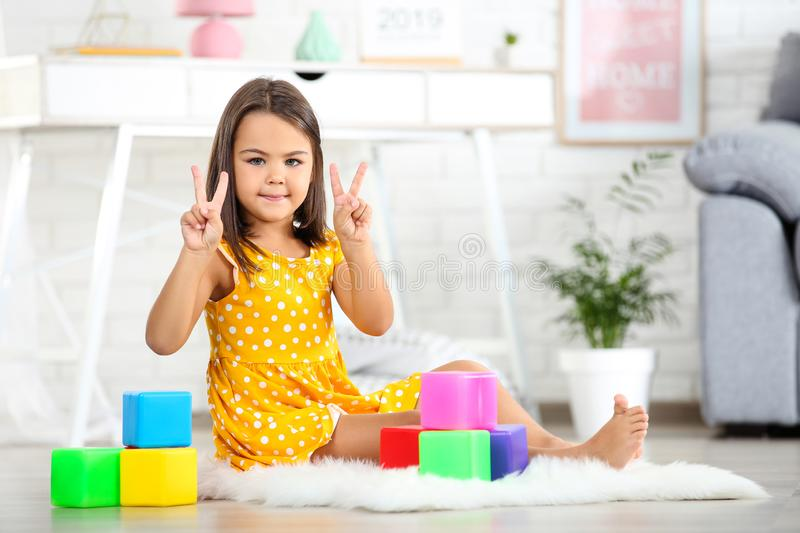 Little girl playing with plastic toys. Beautiful little girl playing with plastic toys at home royalty free stock images