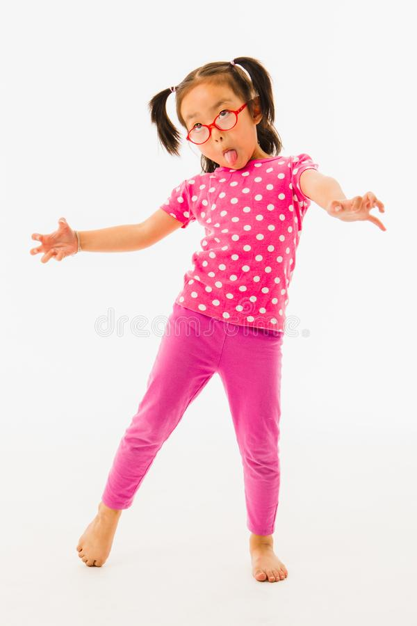 Little girl playing. Portrait of cute little Asian girl wearing red eyeglasses in pink polka dot t-shirt and purple pants, playfully pretending to be a ghost on stock photography