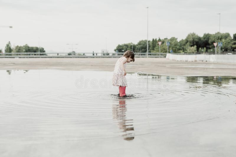 Little girl playing in a puddle, happy. stock photo royalty free stock photo