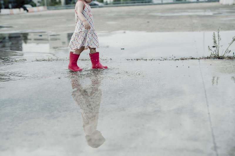 Little girl playing in a puddle, happy. stock photo royalty free stock images