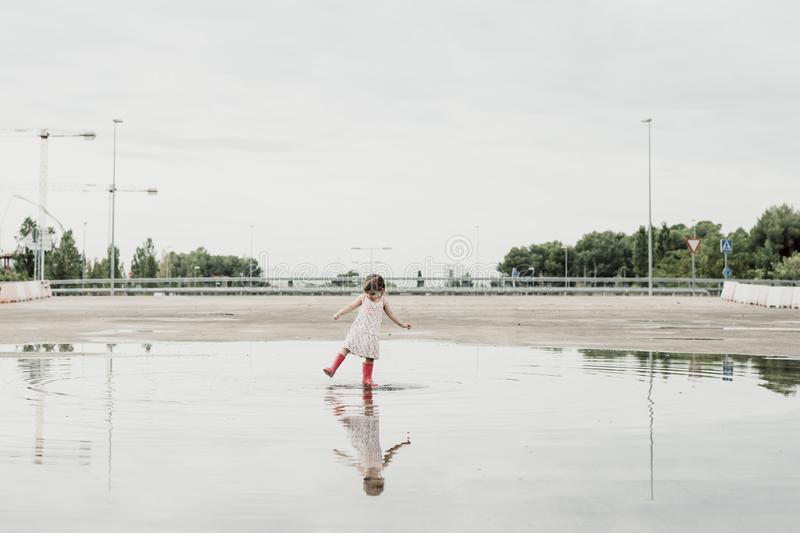 Little girl playing in a puddle, happy. stock photo royalty free stock photography