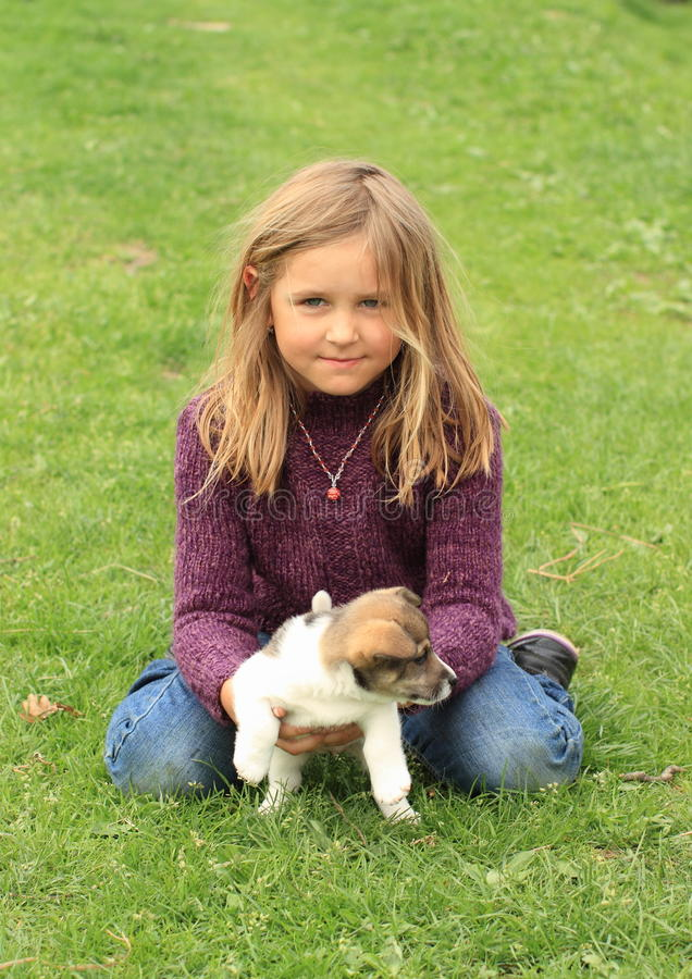 Little girl playing with a puppy. Kneeing little girl in violet pullover and blue pants playing with a brown and white puppy royalty free stock photos
