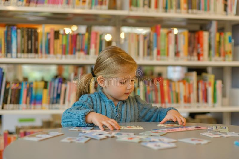 Little girl playing puzzle in a library stock image
