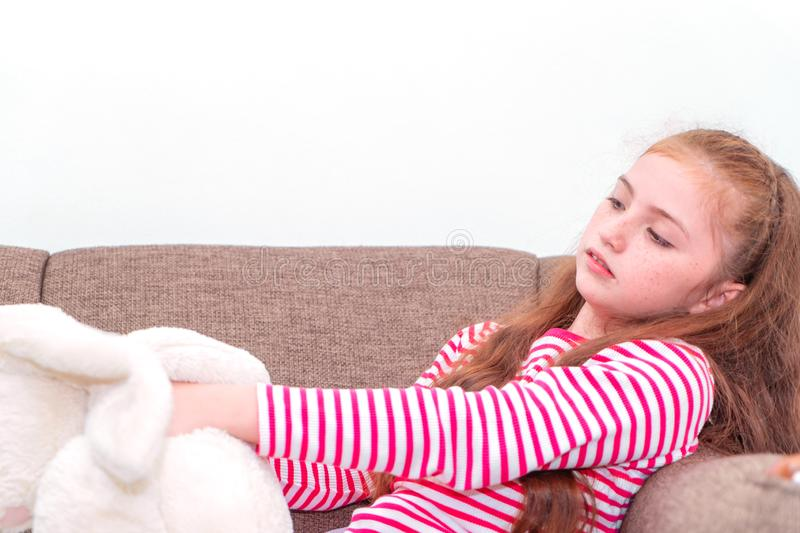 Little girl playing rabbit doll on the Sofa stock photos
