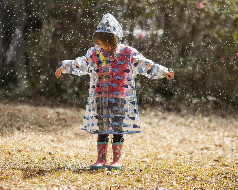 Little girl playing in the rain. Little girl in raincoat and boots playing in the rain royalty free stock image