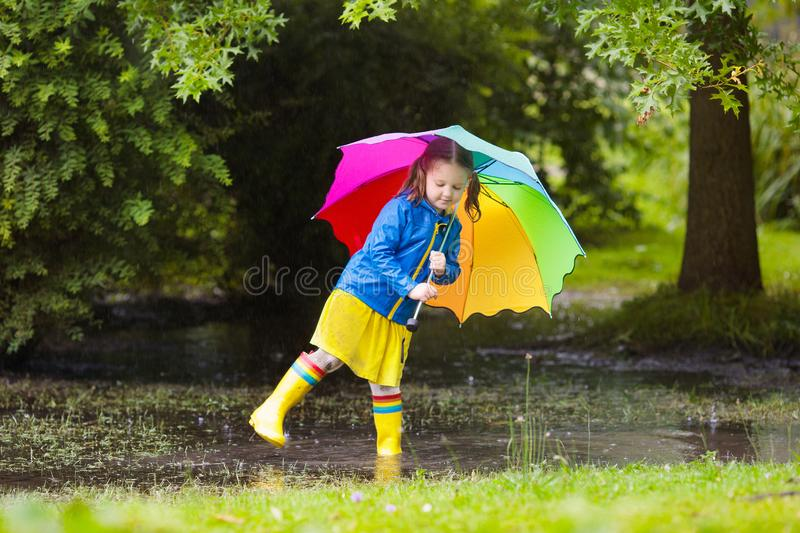 Little girl with umbrella in the rain. Little girl playing in rainy summer park. Child with colorful rainbow umbrella, blue coat walking in the rain. Kid having stock images