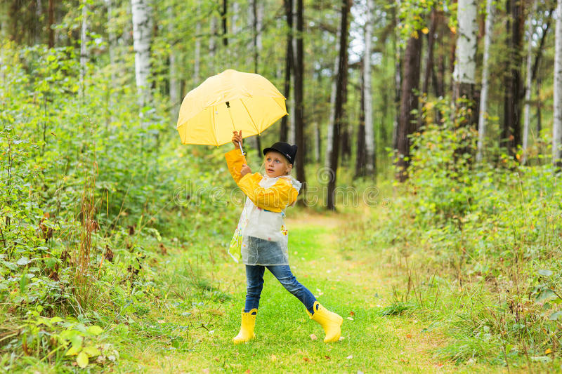 Little girl playing in rainy summer park. Child with yellow rainbow umbrella, waterproof coat and boots jumping in the rain. Outdo stock image
