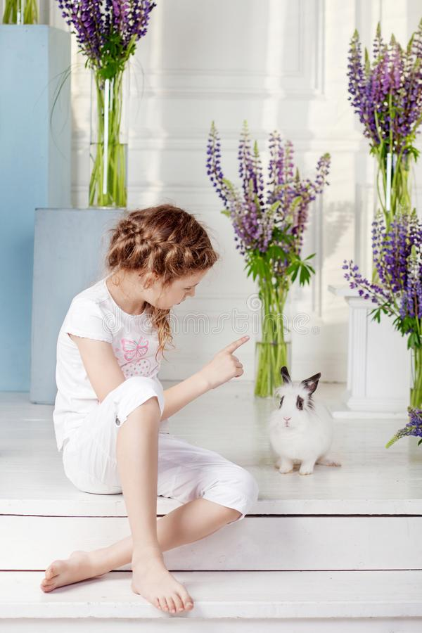 Little girl playing with real rabbit. Child and white bunny on Easter on flower background. Kids and pets play. Fun and friendship stock photography