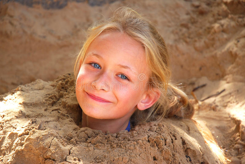 Little girl playing in sand. Outdoor portrait of a cute little blond Caucasian smiling girl child with body buried in sand on the beach that only the head sticks stock images
