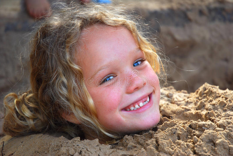 Little girl playing in sandpit stock image