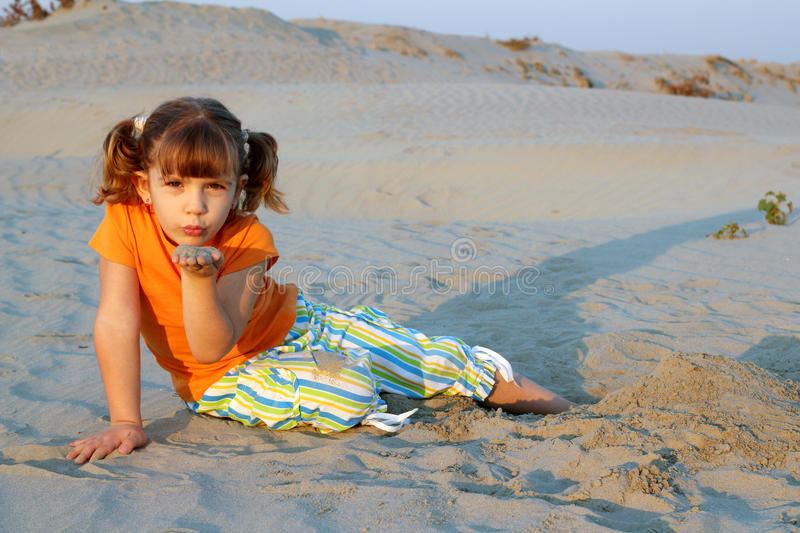 Little girl playing in sand stock images