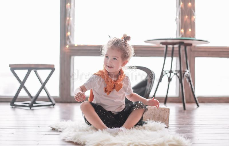 Little girl playing sitting on the carpet in the living room royalty free stock photo