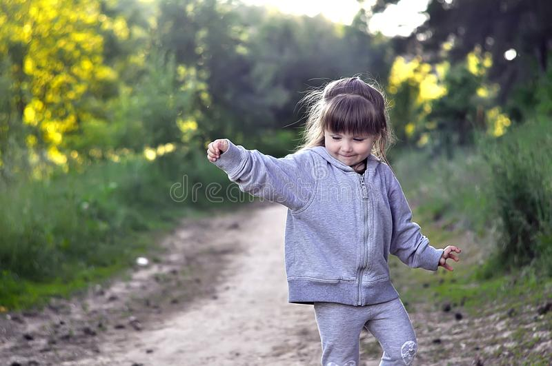 Little girl playing in sunny blooming forest. Toddler child picking flowers. Summer fun for family with children. Little girl playing in sunny blooming garden stock image