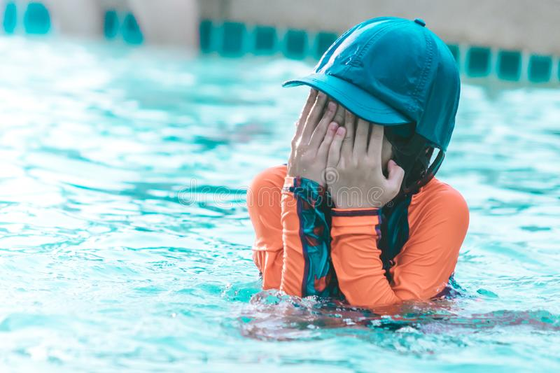 Little girl playing in swimming training pool, wiping water out of her face royalty free stock photography