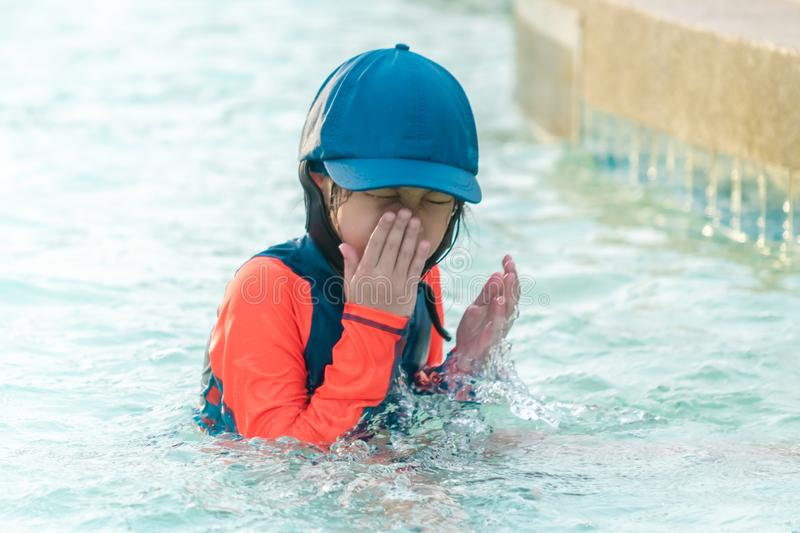 Little girl playing in swimming training pool, wiping water out of her face stock photo
