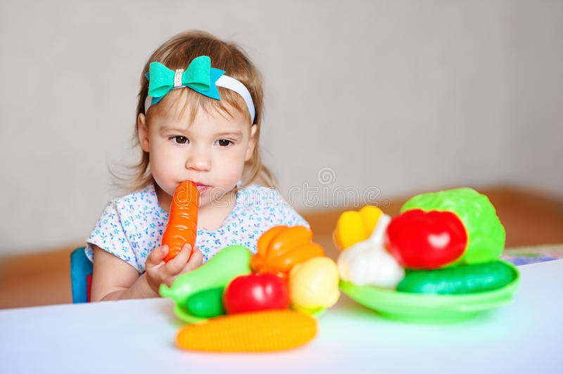 Little girl is playing at the table with vegetables. Child vegetarian. Concept of healthy eating stock image