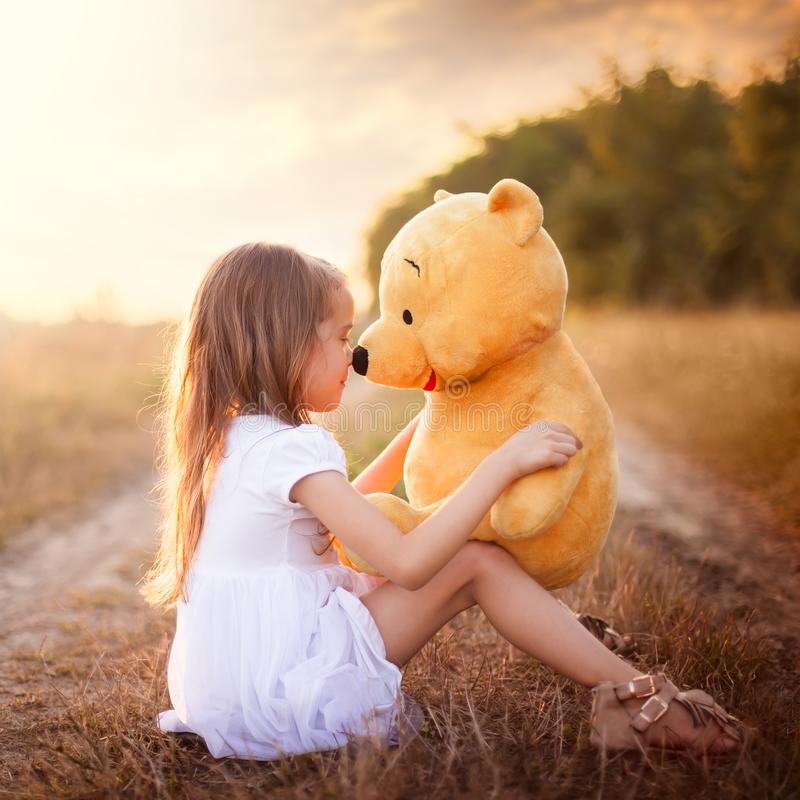 Little girl playing with Teddy Bear on meadow. Beautiful little girl in white dress sitting on the ground and playing with her Teddy Bear on meadow at sunset stock photo
