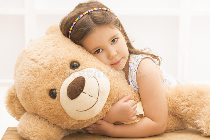 Little girl playing with teddy bear. Portrait of expressive little girl hugging huge plush bear, indoor shot on white room stock photo