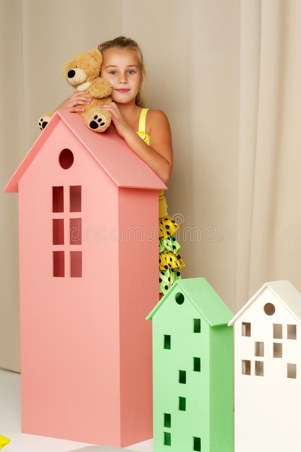 Little girl playing with a teddy bear in a toy wooden house. Cute little girl playing with a teddy bear in a toy wooden house. The concept of family, happy stock photo