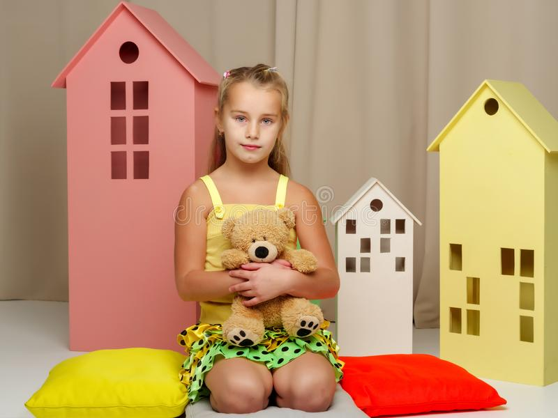 Little girl playing with a teddy bear in a toy wooden house. Cute little girl playing with a teddy bear in a toy wooden house. The concept of family, happy royalty free stock images