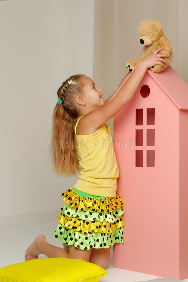 Little girl playing with a teddy bear in a toy wooden house. Cute little girl playing with a teddy bear in a toy wooden house. The concept of family, happy royalty free stock photos