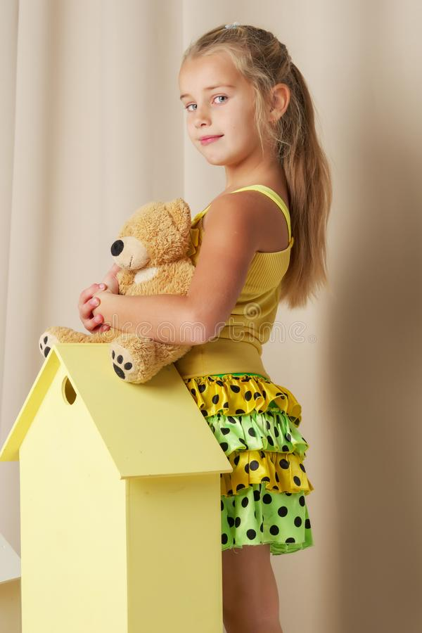 Little girl playing with a teddy bear in a toy wooden house. Cute little girl playing with a teddy bear in a toy wooden house. The concept of family, happy stock photos