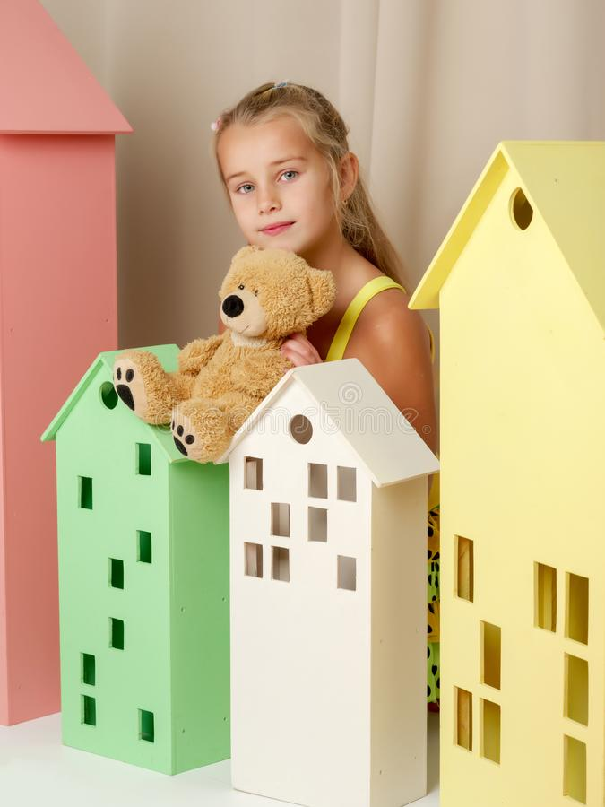 Little girl playing with a teddy bear in a toy wooden house. Cute little girl playing with a teddy bear in a toy wooden house. The concept of family, happy stock images