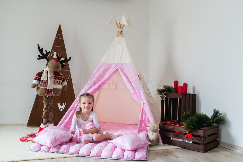 Little girl playing in a tent. royalty free stock photo