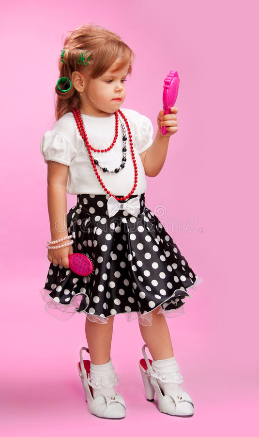 Little girl playing to be her bigger sister royalty free stock image