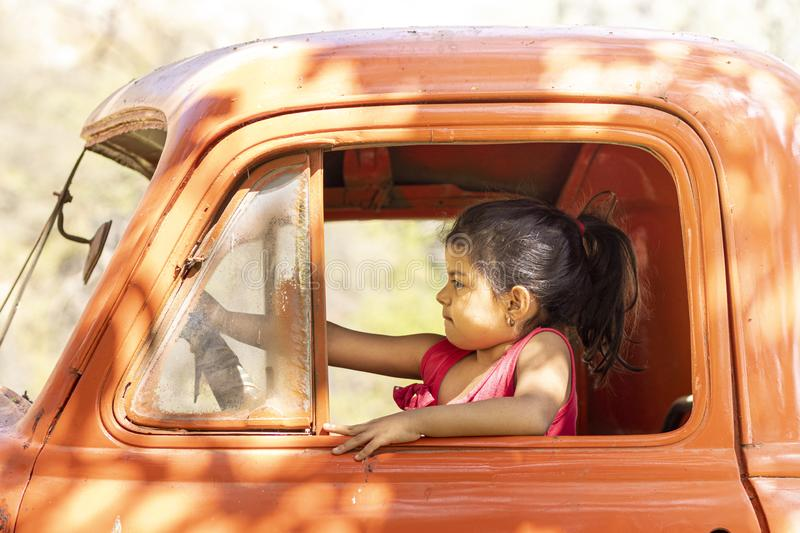 Little girl playing to drive cargo truck royalty free stock image