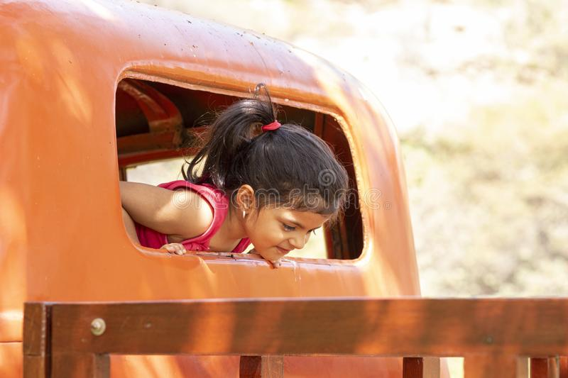 Little girl playing to drive cargo truck royalty free stock photo