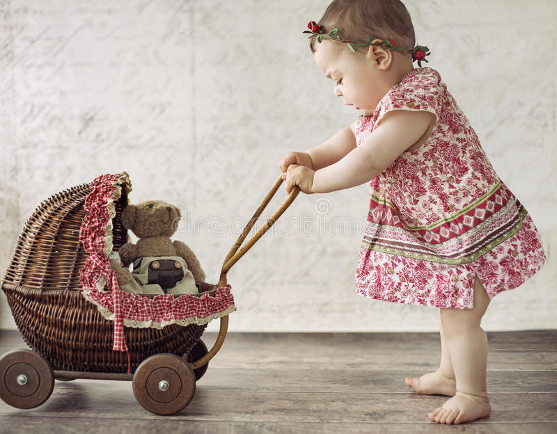 Little girl playing the toy carriage royalty free stock photography