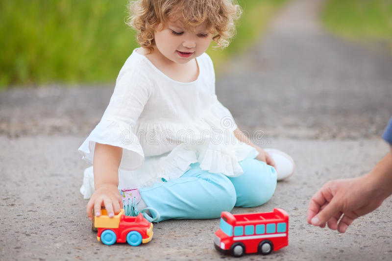 Little girl playing with toy cars with her father. Father play with his toddler daughter in boys games. Two color cars royalty free stock photo